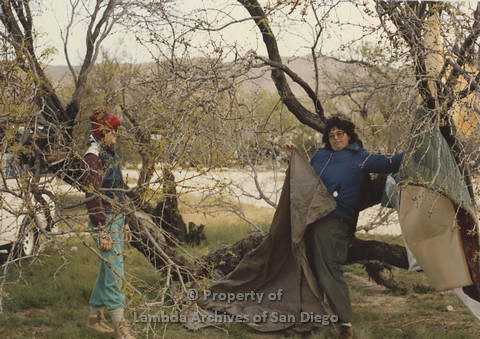 P024.071m.r.t Cathy Moore's 34th Birthday, Halley's Comet Weekend, Anza Borrego Desert 1986: 2 people behind a tree, one holding pieces of a tent