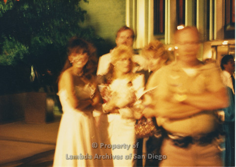 P024.138m.r.t Myth California Protest, San Diego, June 1986: blurry photo of people standing behind a police officer