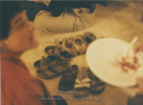 Alix Dobkin Concert, 1985 in the home of Carol Cianfarani:  Lesbian Artist Nancy Gordon (left) with a close-up of Birkenstocks in a circle on the carpet.