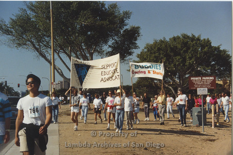 "P001.118m.r.t AIDS Walk 1991: People walking holding 2 banners (AIDS Foundation San Diego: Support, Educate, Advocate) and (""Buddies"" Caring & Sharing)"