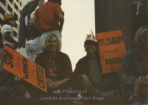 P024.098m.r.t Myth California Protest, San Diego, June 1986: 2 people sitting and holding signs