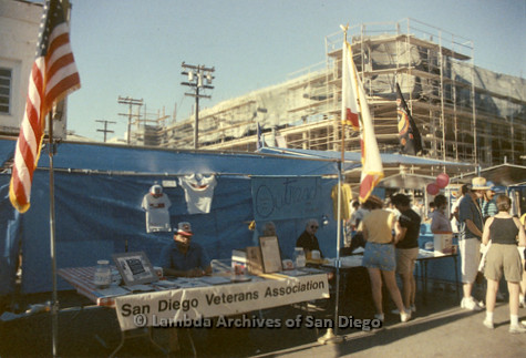 "P018.007m.r.t San Diego Pride Festival 1988: People visiting booths, sign reads: ""San Diego Veterans Association"""