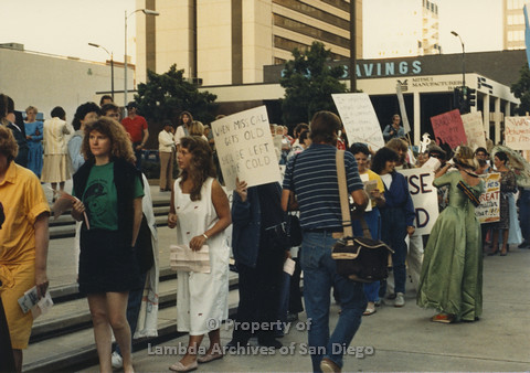 P024.106m.r.t Myth California Protest, San Diego, June 1986: candid shot of crowd, person in the center holding a sign (When Miss. Cal gets Old She wil be Left in the Cold)