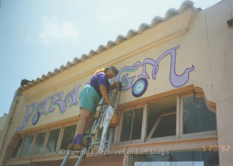 """P167.063m.r.t Paradigm Women's Bookstore: Woman painting """"G"""" in """"Paradigm"""" above store front with teal color"""