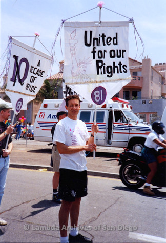 P018.120m.r.t San Diego Pride Parade 1994: Frank Nobiletti holding Lesbian and Gay Archives banner