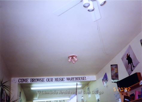 """P167.008m.r.t Paradigm Women's Bookstore: Partial ceiling and sign that reads: """"Come browse our music warehouse"""""""