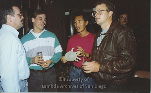 P001.158m.r.t 1st Anniversary 1991: Four men. One holding an inflated plastic glove