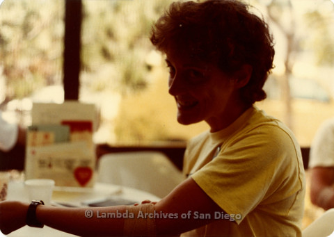 Blood Sisters blood drive 1983: A woman  showing off her bandage post blood-draw