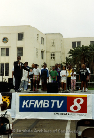 "P240.047m.r.t The Center at AIDS Walk 1994: African American Children on ""KFMB TV 8"" stage, announcer talking into microphone"