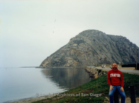 P338.072m.r.t Charles McKain wearing a red Stanford sweatshirt standing in front of Morro Rock in Morro Bay, California