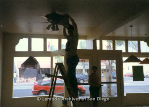 P169.032m.r.t Paradigm Women's Bookstore - Moving in: Woman on ladder installing ceiling fan