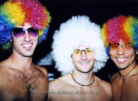 P184.050m.r.t Nightmare On Normal Street: Close up of three men in rainbow afro wigs, embracing/posing for a photo.