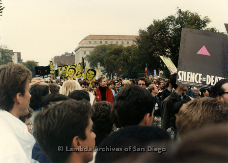 "P323.003m.r.t 1987 March on Washington: View over top of crowd, protesters holding Ronald Reagan ""AIDSGATE"" signs"