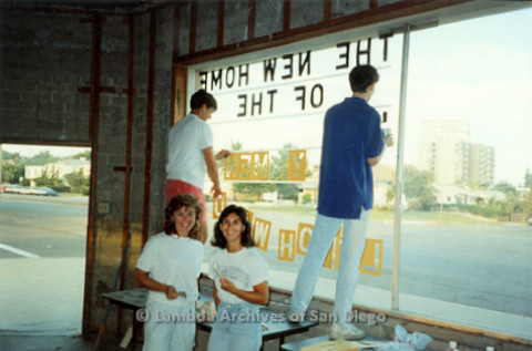 P022.008m.r.t The Center, Normal Street: Two women posing inside Center, in front of window where two men are painting sign
