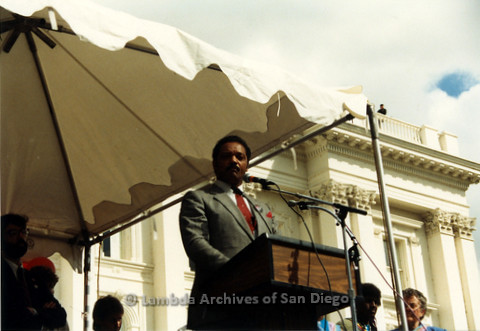 P019.135m.r.t March on Sacramento 1988 / Pre Parade gathering: Jessie Jackson speaking at podium on stage in front of City Hall