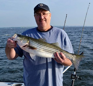 Photo of man holding striped bass