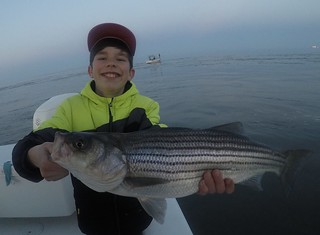Photo of boy holding a nice striped bass he caught and released