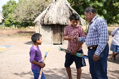 Minister of Indigenous Peoples' Affairs, Hon. Sydney Allicock interacts with two young lads.