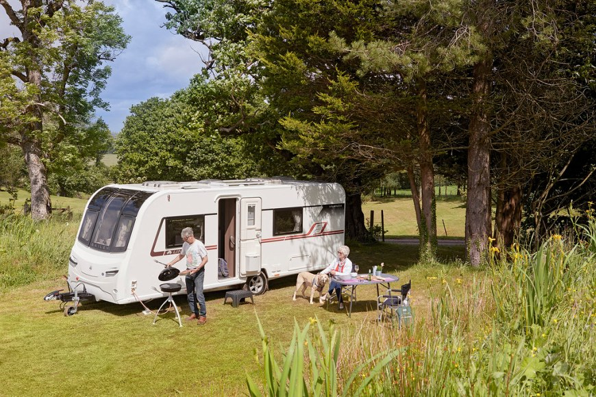 Exterior of a 2 berth caravan with people making a BBQ near it