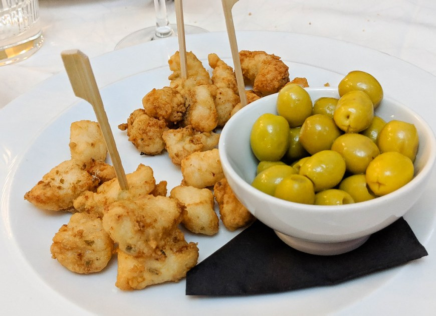 A plate of cazon and a bowl of olives