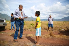 Minister of Indigenous Peoples' Affairs, Hon. Sydney Allicock distributes a kite to a young lad.