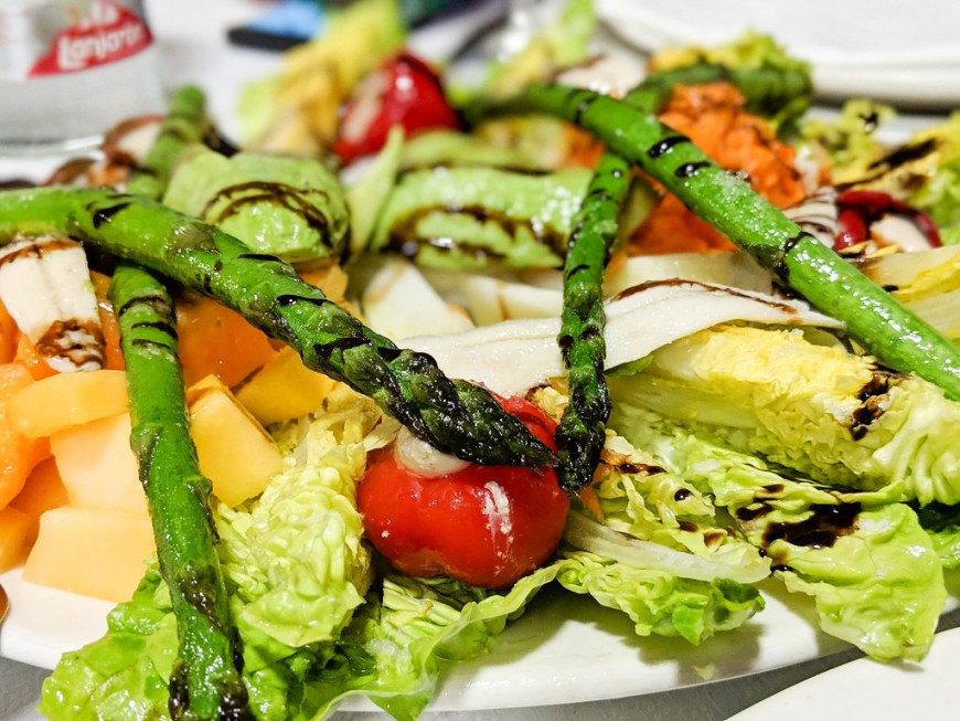 A plate of salad with asaparagus, piquill peppers, mango, papaya, anchovies