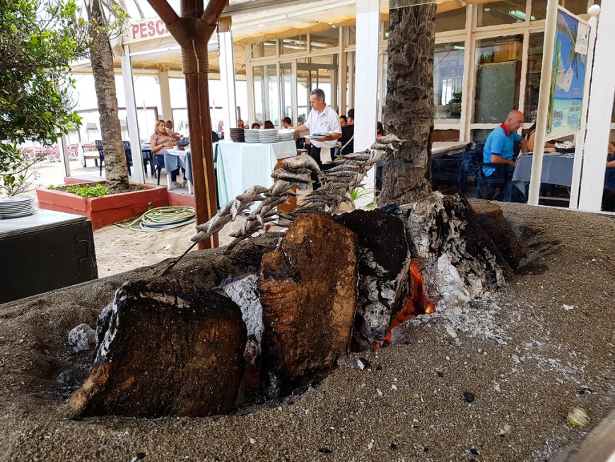 A typical chiringuito grilling fish over a pile of wood on fire