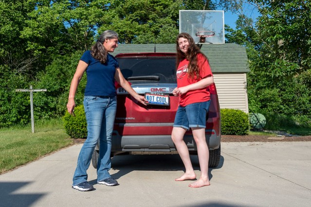 """Krissy and Athena pose in front of Athena's new car, to which the """"Not Cool"""" plates are being attached."""