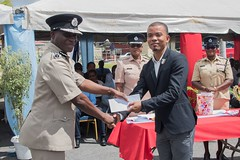 An Officer receives an award from Commissioner of Police, Leslie James.