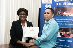 A participant of the National Capacity Building on Web Accessibility program receives his certificate from Minister of Public Telecommunications, Hon. Catherine Hughes.