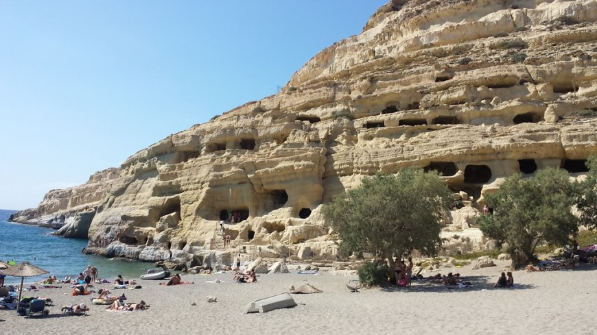 A beach next to a cliff full of little caves