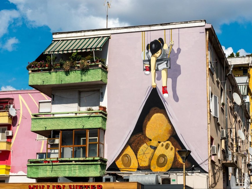 A communist building painted with a graffiti depicting a little girl on a swing pulling up a sheet underneath which there is a big teddy bear