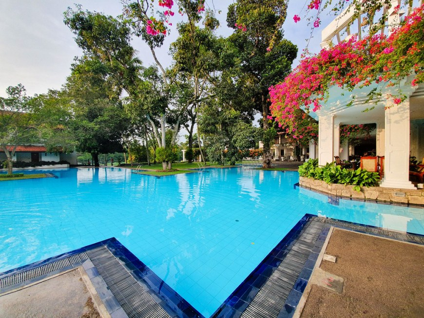 A large pool belonging to a hotel in Kandy. The pool doesn't have a definied shape. In the photo there are three corners, forming a triangle. The pool spreads all the way to the back of the photo. On the right hand side a part of the bar of the hotel can be seen, which has white columns and it is covered in pink flowers.