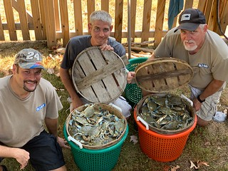 Photo of three men with two bushels of blue crab
