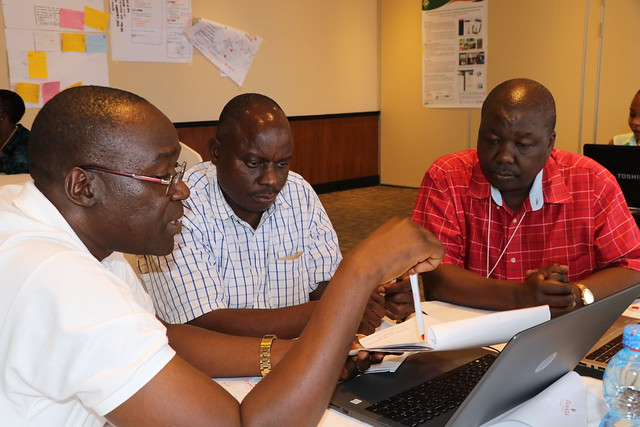 Patrick Okori (ICRISAT; left), Chrispinus Rubanza (UDOM; center) and Ben Lukuyu (ILRI; right) in a discussion during the Africa RISING East and Southern Africa Project review and planning meeting held in Dar es Salaam, Tanzania on 10 – 11 September 2019.