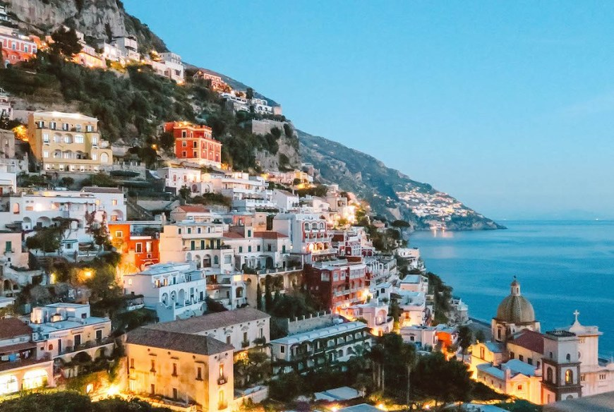 A view of the hill houses in Positano by night, in which the houses have the lights on
