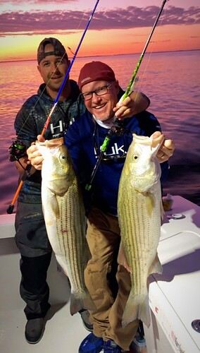 Photo of two men holding large striped bass