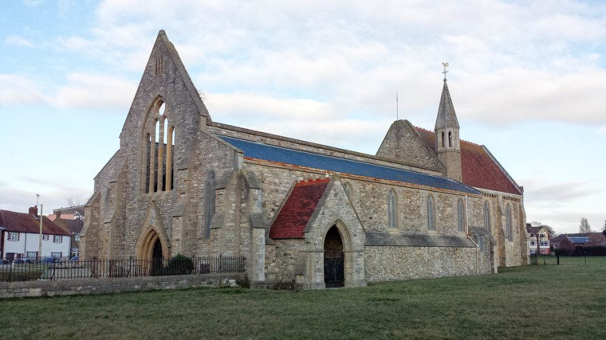 The remains of the stone church, without a roof. The church takes the entire space of the photo. It has one small tower.