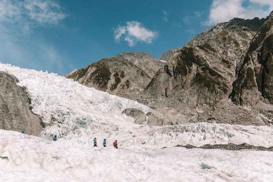 3 people walking on top of a glacier, behind a rocky mountain cliff