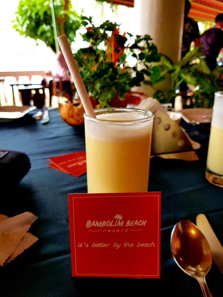 """A glass of mango lassi with a paper straw in it. In front of the glass there is a red label saying """"Bambolim Beach - It's better by the beach""""."""