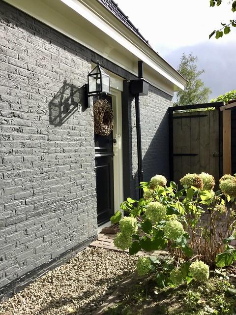 Grijze zijgevel woonboerderij voordeur