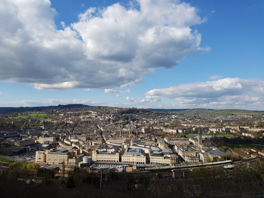 An aerial view of the city to Bath, on a sunny day. The sky is blue, with a big fluffy cloud in the middle.