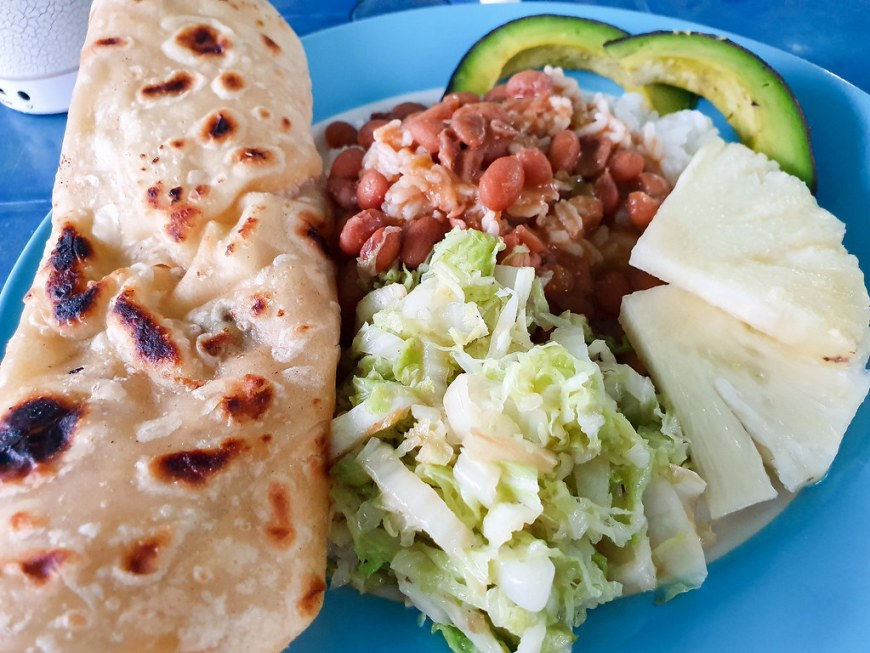 A flat bread takes a third of the picture, on the left. The rest of the plate is filled with beans, cabbage salad, 2 slices of green avocado and 2 slices of pineapple.