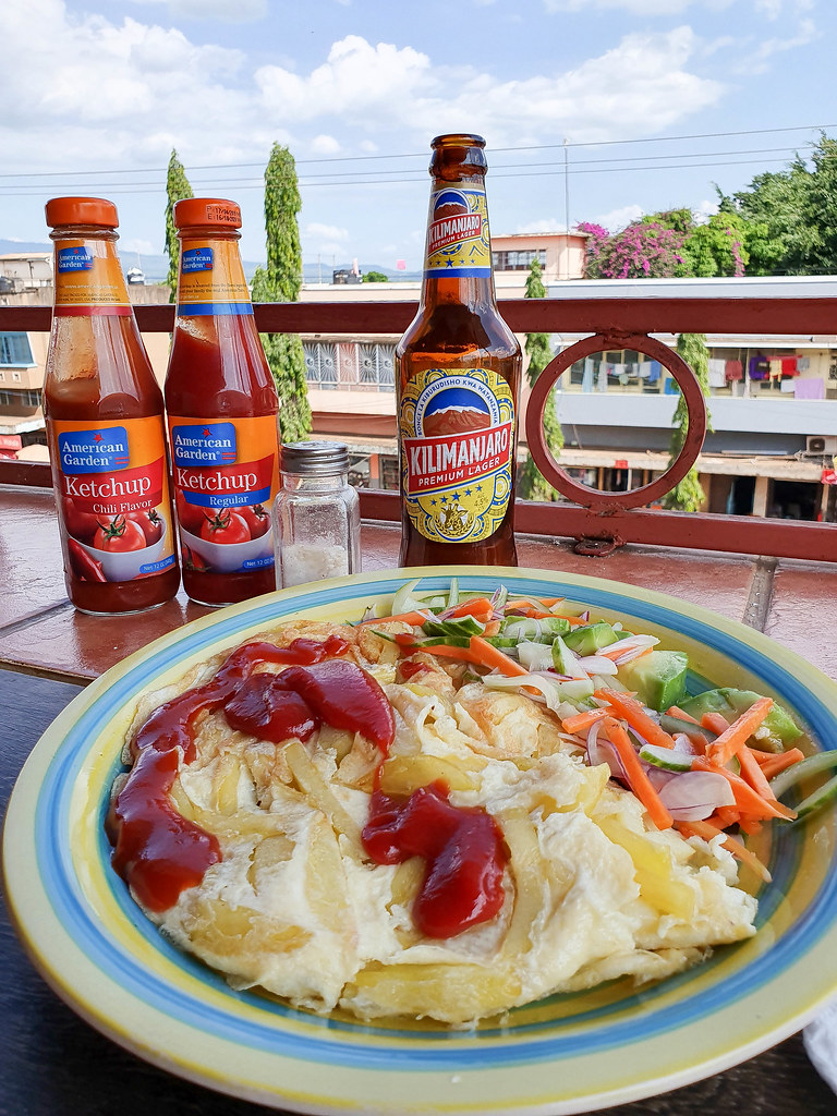 In the foreground there is a plate with chips inside an omelette, covered with ketchup. On the side, there is a carrot, onions and green peppers salad. In the background of the photo there are 2 bottles of red ketchup, one normal and one with chili. There is also a bottle of Kilimanjaro beer. The table is at the edge of the terrace so nearby rooftops can be seem, together with the blue sky on top of the photo.
