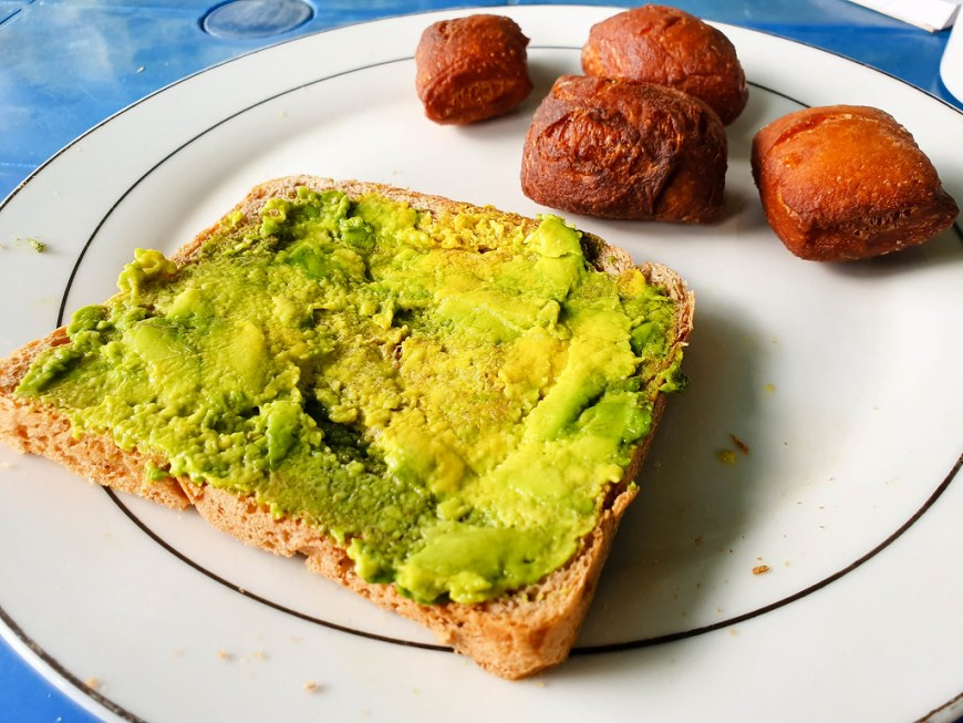 A slice of bread with green avocado spread on it. Besides it there are 4 mandazi - brown from frying and square shaped.