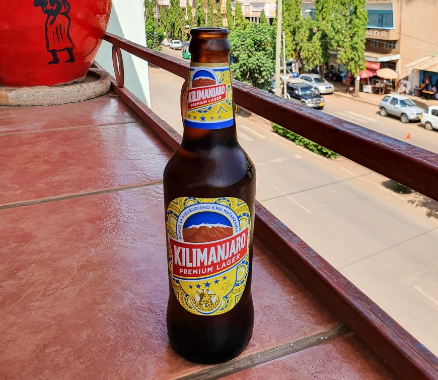 A bottle of Kilimanjaro beer, on the terrace of a restaurant. Down below there is a street with cars parked on the side. Behind the bottle there is a red flower pot with an African lady drawn in black pencil on it.