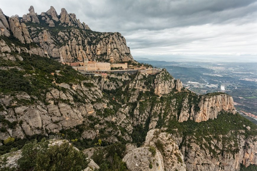 montserrat monastery on the side of the cliffs. in the background you can see the valley below, very far