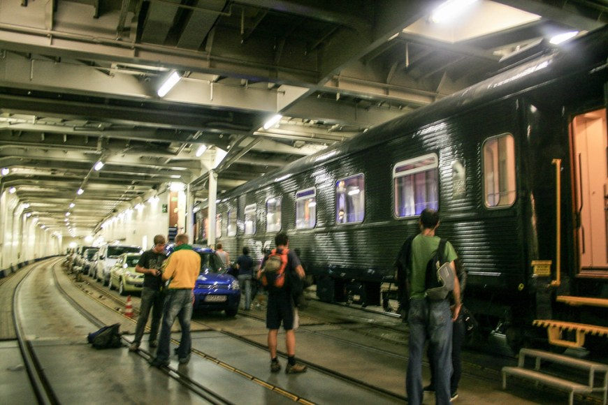 A train loaded on the ferry, next to a row of cars. There are a few people next to the train, looking around