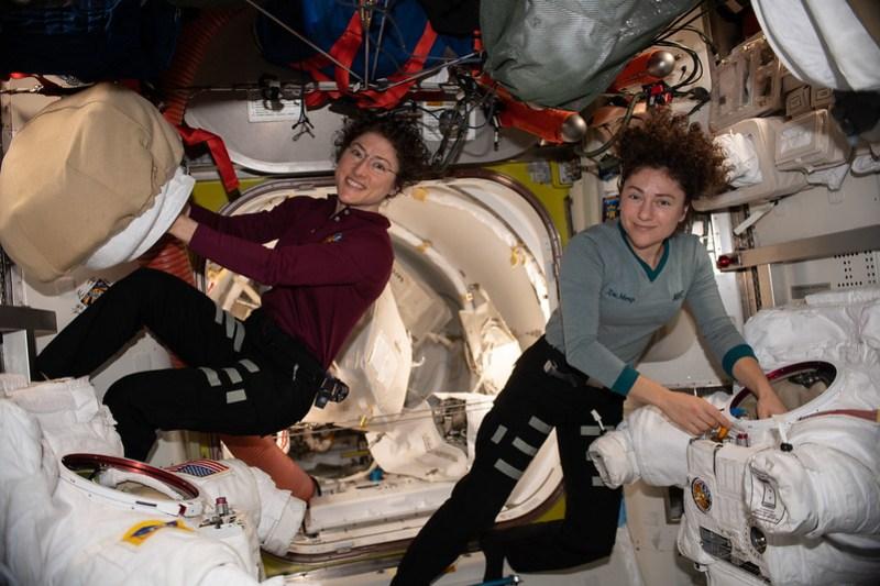 NASA astronauts Christina Koch and Jessica Meir work on their U.S. spacesuits