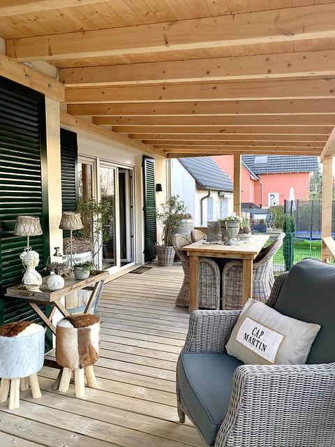Rieten tuinset onder veranda met houten vloer